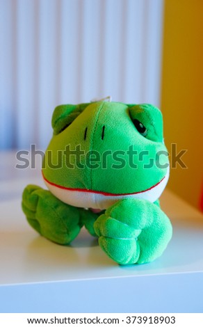 Green plush frog sitting on table - stock photo