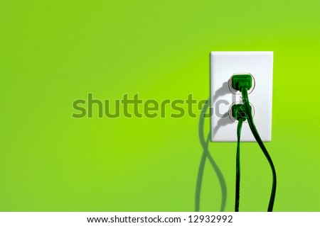 Green power cords in electric outlet on a green colored wall - green energy concept - stock photo