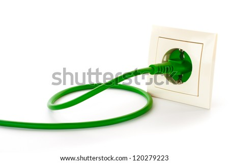 Green power plug into power outlet against a white background - stock photo