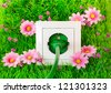 Green power plug into power outlet on the grass with flowers - stock photo