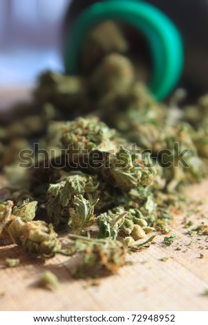 Green prescription cannabis spilling out of a bottle (shallow depth of field) - stock photo