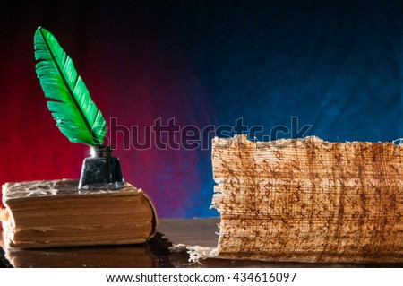 Green quill pen and a backlit papyrus sheet with its particular texture on a blue and brown background - stock photo