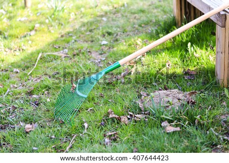 green rake on the grass with wooden bench - prepared for gardening - stock photo