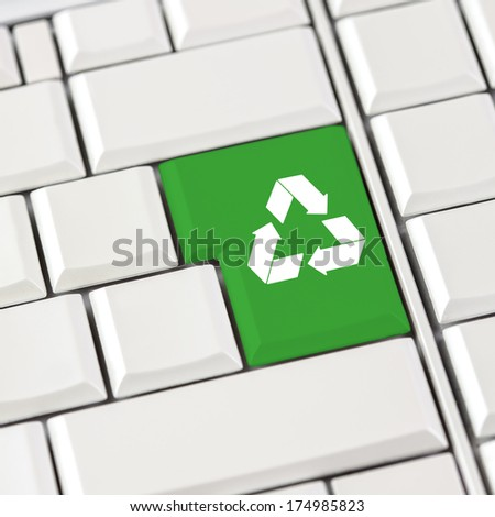 Green recycle icon on a computer keyboard with blank white keys conceptual of recycling materials to save the planet. - stock photo