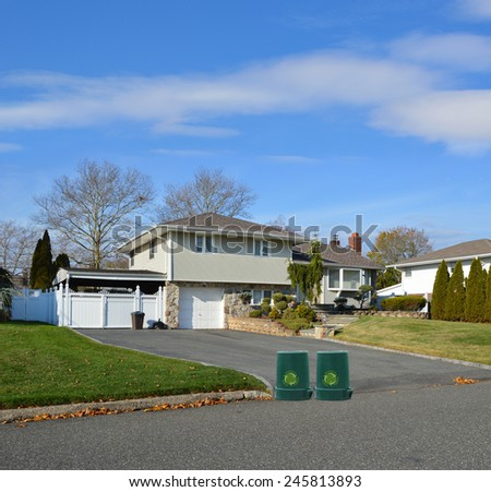 Green recycle, reuse, reduce, trash container Suburban High Ranch Home with Siding and Stone Landscaped beautiful sunny blue sky clouds residential neighborhood USA - stock photo