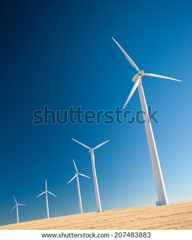 Green renewable energy concept - wind generator turbines in sky - stock photo