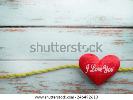 green ribbon tape and heart on vintage wooden background - stock photo