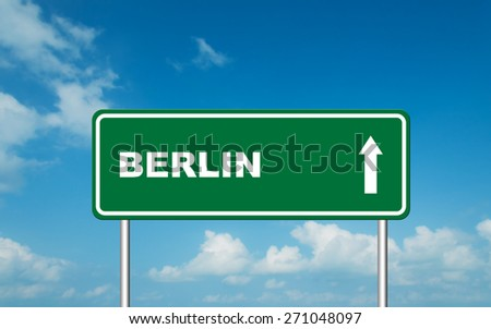 Green road sign board with straight direction to Berlin with sky background - stock photo