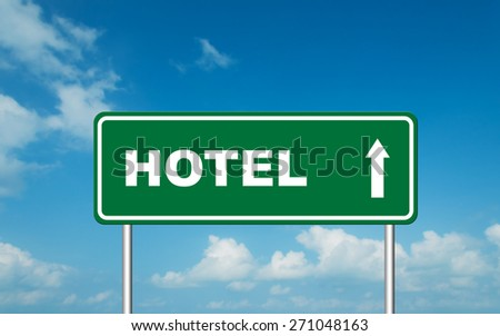 Green road sign board with straight direction to Hotel with sky background - stock photo