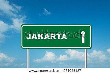 Green road sign board with straight direction to Jakarta with sky background - stock photo
