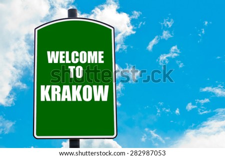 Green road sign with greeting message WELCOME TO KRAKOW isolated over clear blue sky background with available copy space. Travel destination concept  image - stock photo