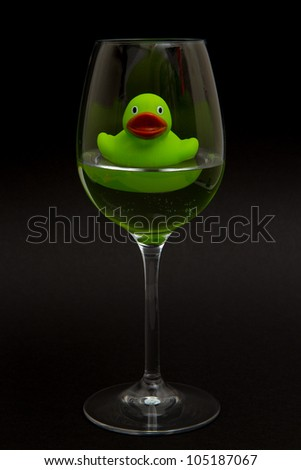 Green rubber duck in a wineglass with water (black background) - stock photo