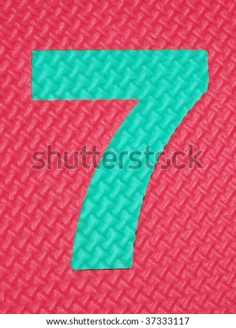 Green rubber number 7 on red rubber background with tread plate texture - stock photo