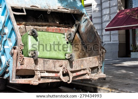 green rubbish container in a rubbish truck - stock photo