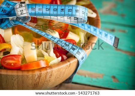 Green salad concept and measure tape on a plate - stock photo