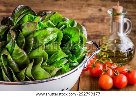 green salad ingredients: organic lettuce, cherry tomatoes and olive oil - stock photo