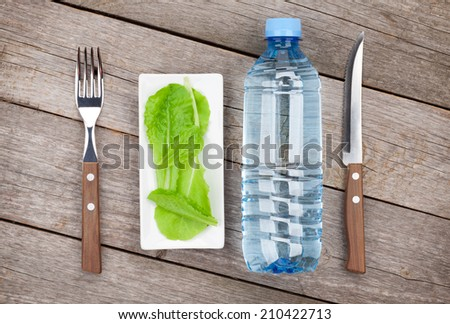 Green salad leaves and water bottle. Healthy food on wooden table - stock photo