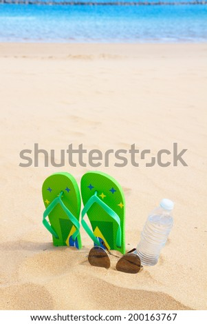 green  sandals  on sandy beach with bottle of clear water and glasses - stock photo