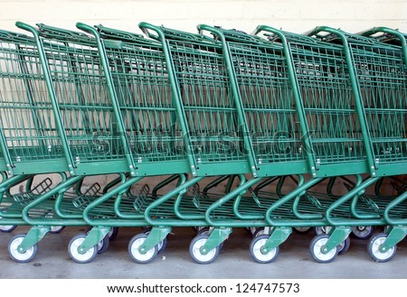 Green shopping carts together in a line up. - stock photo