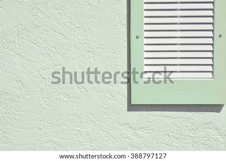Green shutter and exterior stucco wall - stock photo
