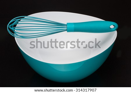 Green silicone pastry brush and soup plate isolated on black - stock photo