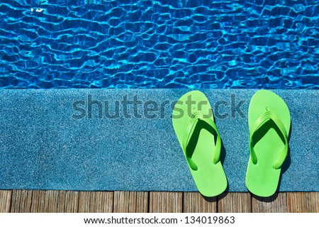 Green slippers by a swimming pool - stock photo