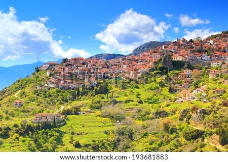 Green slopes surrounding the mountain town of Arachova near Parnassus Mountains, Greece - stock photo