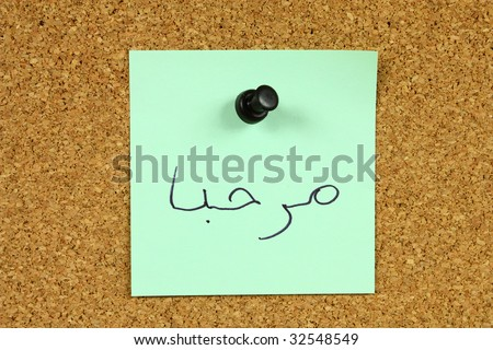 """Green small sticky note on an office cork bulletin board. Word """"marhaba"""" in Arabic, which means """"hi"""" or """"hello"""". - stock photo"""