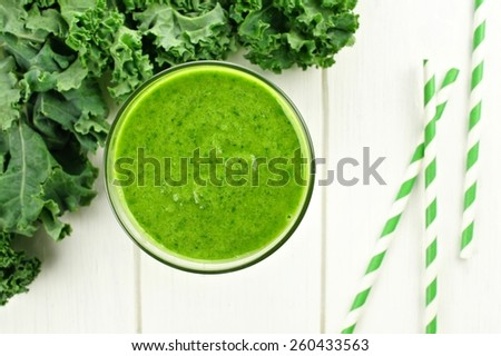 Green smoothie in a glass with kale, overhead view on white wood - stock photo