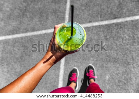 Green smoothie woman drinking plastic cup breakfast meal takeaway to go after morning run on city streets. Healthy lifestyle sporty person pov of hand holding glass with running shoes feet selfie. - stock photo