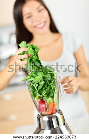 Green smoothie woman making vegetable smoothies with blender. Healthy eating lifestyle concept portrait of beautiful young woman preparing drink with spinach, carrots, celery etc at home in kitchen. - stock photo