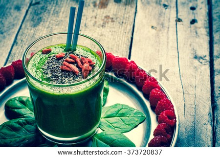 Green smoothies served on a plate with baby spinach and arranged around the raspberries. Smoothie sprinkled with chia seeds and goji berries. - stock photo