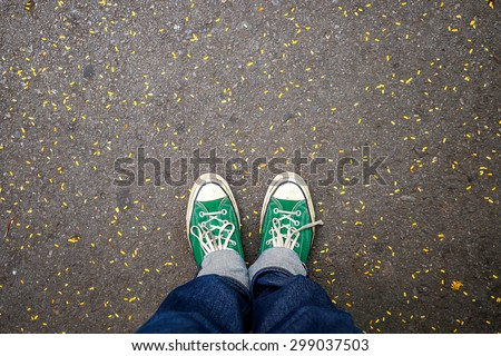 Green Sneakers shoes walking on concrete look top view , Canvas shoes on dirty road , Hister life - stock photo