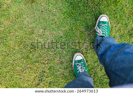green Sneakers shoes walking on green grass top view , Canvas shoes walking on green grass - stock photo