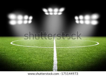 Green soccer field, bright spotlights, - stock photo