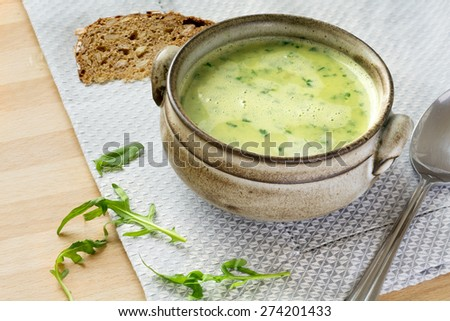 green soup from arugula with cream in a rustic bowl, some leaves as garnish, spoon and bread - stock photo