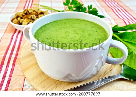 Green soup puree in a bowl, spinach leaves, spoon derevyannoydoske, croutons on fabric background - stock photo