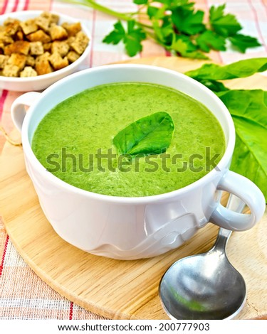 Green soup puree in a bowl with green leaf spinach, spoon on the board, crunches on fabric background - stock photo