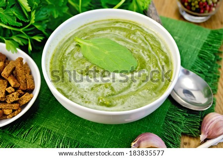 Green soup puree in white bowl with spoon, napkin, parsley, croutons, pepper, garlic on a wooden boards background - stock photo