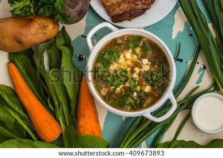 Green soup with eggs and ingredients for his cooking. Old background - stock photo