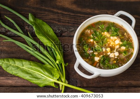 Green soup with eggs and ingredients for his cooking. Wooden background - stock photo