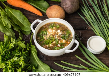 Green soup with eggs and ingredients for his cooking. Wooden background. Top view - stock photo