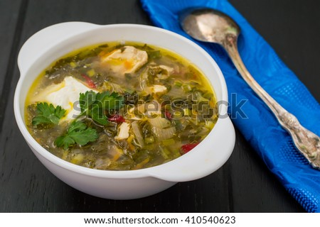 Green soup with sorrel, parsley and sour cream. Wooden blackbackground. Top view - stock photo