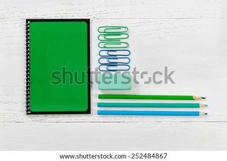 Green spiral notepad with pencils, eraser, and paper clips on desktop. Pattern in colors of green and blue with a white wooden background.  Educational or business concept.  - stock photo