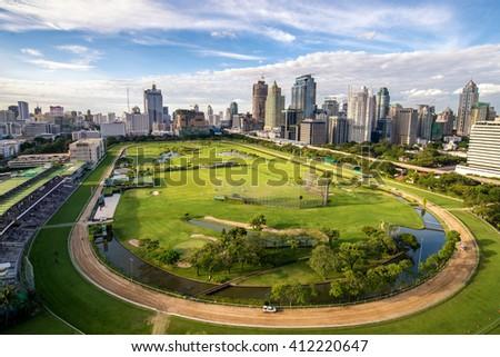 green stadium field of horserunner in center on bangkok cityscape background - stock photo