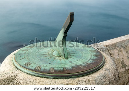 Green stained copper or brass sundial fixed to stone wall of castle overlooking the ocean far below - stock photo