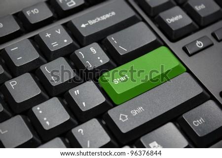 green start button on black computer keyboard - stock photo
