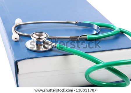 Green stethoscope lying on a thick blue book - stock photo