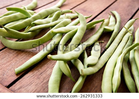 green string beans on wooden table - stock photo