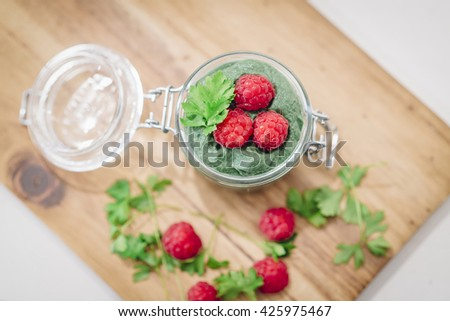 Green super-useful mousse with raspberries. The view from the top. Glass jar mousse on a Board laid out with raspberries and sprigs of parsley - stock photo